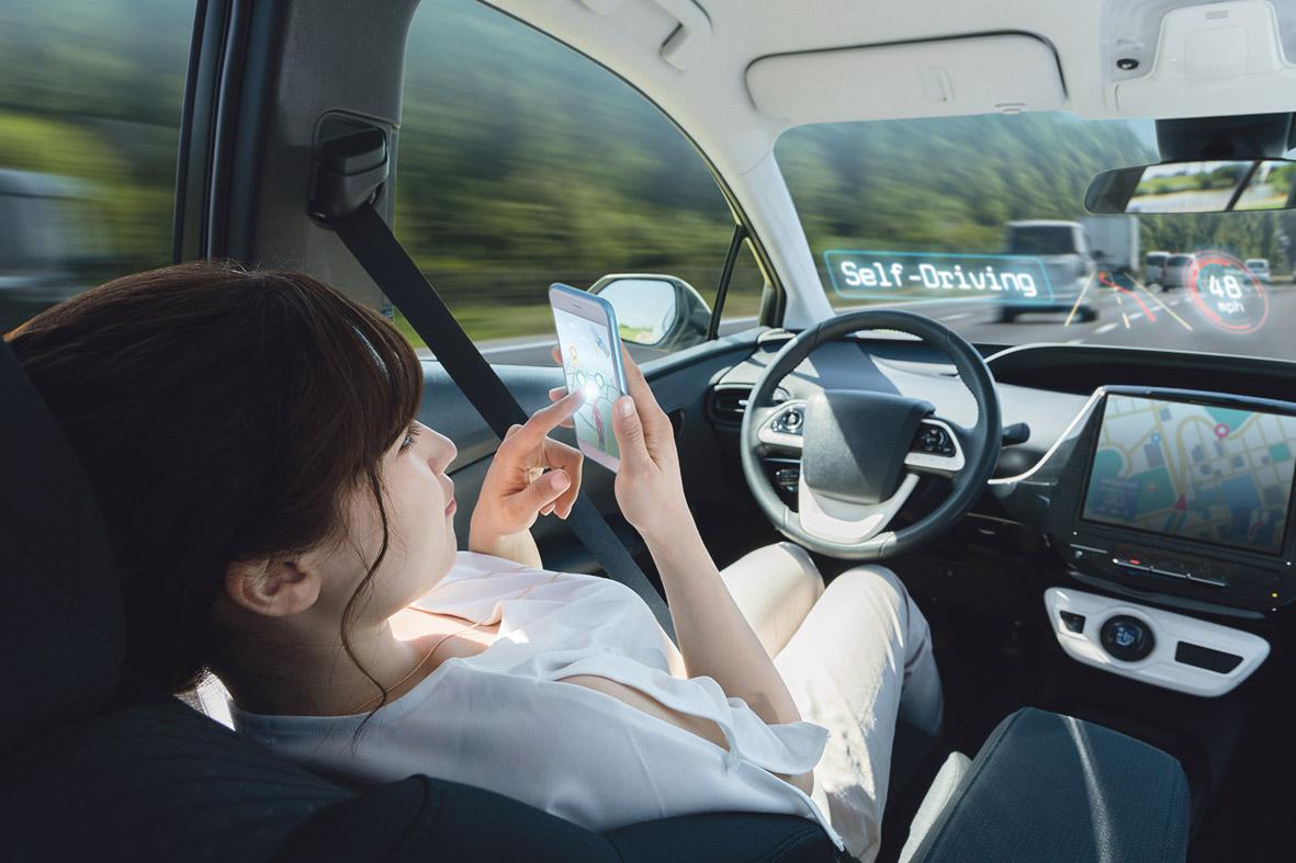 Eine Autofahrerin sitzt entspannt im Auto, da es selbständig fährt.