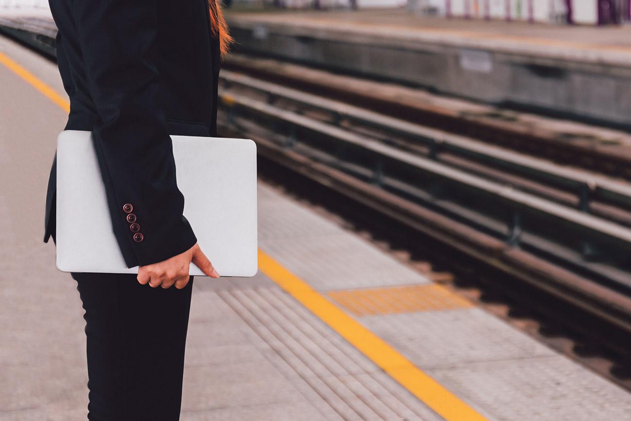 Dienstreisende steht mit ihrem Laptop am Bahnhof.
