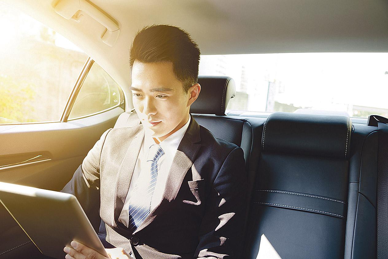 Geschäftsmann im Auto arbeitet am Tablet. Thema: Selbstfahrendes Auto
