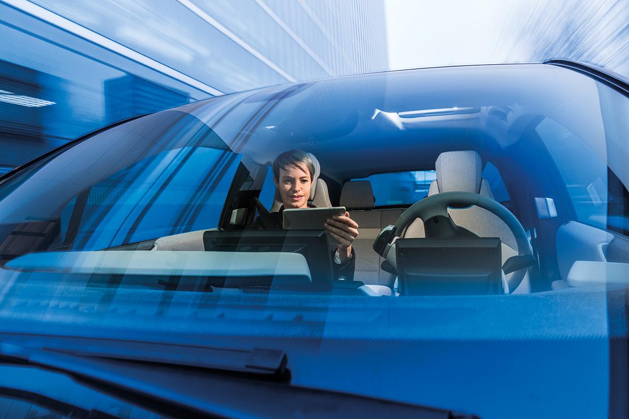 Autonomes Fahren: Frau sitzt mit Tablet in der einen Hand auf dem Beifahrersitz. Der Fahrersitz bleibt frei.