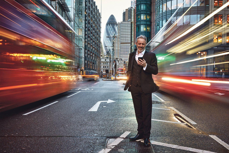 Ein Mann mit Smartphone steht auf der Straße. Um ihn herum fließt der Verkehr.