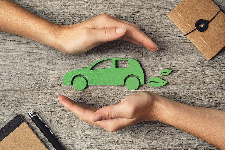 grünes Auto wird von zwei Händen geschützt. Thema: Neue Ideen der Energieversorgung