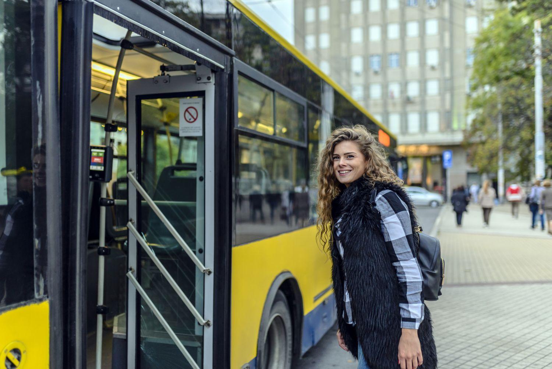 Junge Frau steigt in einen Bus ein.