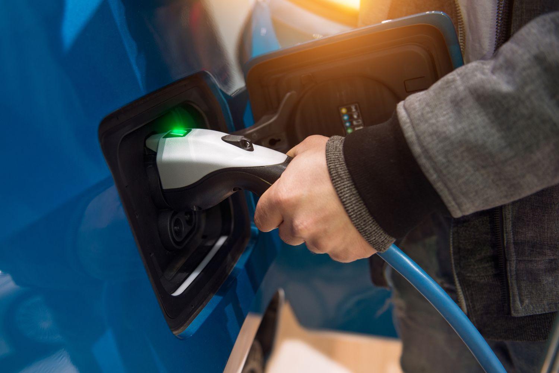 Mann lädt Elektrofahrzeug auf. Thema: Alternative Energiequellen für das Auto